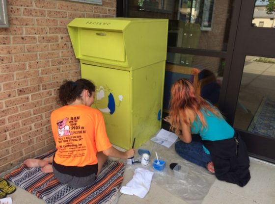 Janelle and Taylor painting the book return box.