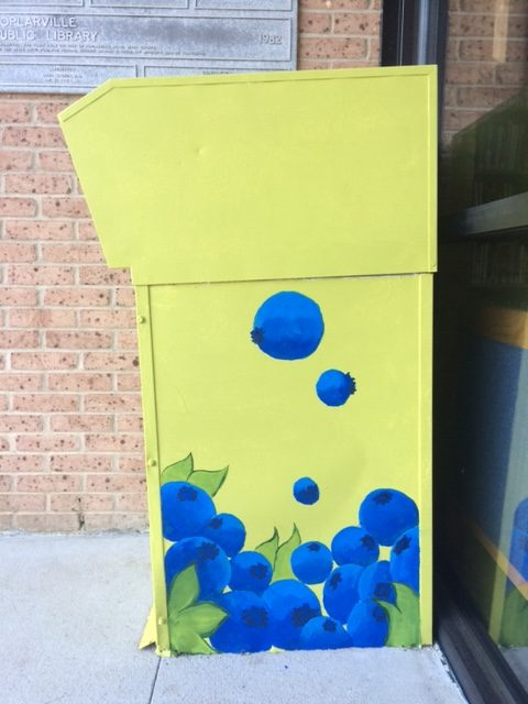 The book return box painted in the theme of blueberries.